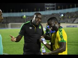Jamaica's coach Theodore Whitmore talks with Kemar Lawerence after the Reggae Boyz played The Cayman Islands at the National Stadium on September 9, 2018.