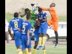 Hydel High School goalkeeper Shaquan Davis (right) leaps for a ball the Walker Cup final against Excelsior High School at the Stadium East field last season.
