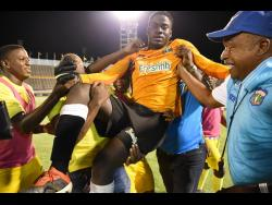 File Prince Daniel Smith (centre), goalkeeper of Clarendon College, is carried off the field by teammates and supporters after they defeated Jamaica College on penalties to win the Olivier Shield title for 2019.