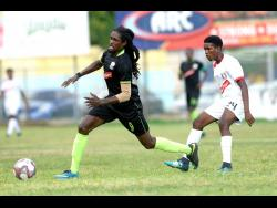 Tajahe Dixon (left) of Molynes United FC beats Arnett Gardens' Damari Deacon to a loose ball during their RSPL encounter at the Waterhouse Mini Stadium on Sunday, September 22, 2019.
