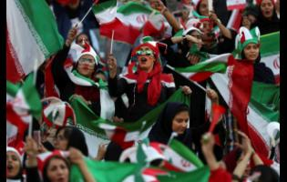 AP Iranian women cheer during a football match between their national team and Cambodia  at the Azadi Stadium in Tehran, Iran, yesterday.