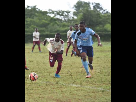 Herbert Morrison Technical High School's Marc Graham (left) races Holland High School's Demar Chambers to collect the ball in their ISSA/WATA DaCosta Cup game at the Holland High School Field on Monday, October 8, 2018.