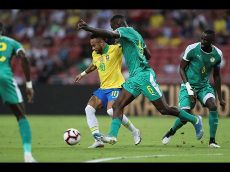 Brazil's Neymar (centre) and Senegal's Salif Sane in action during the Brazil Global Tour 2019 international friendly in Singapore yesterday. The match ended 1-1.